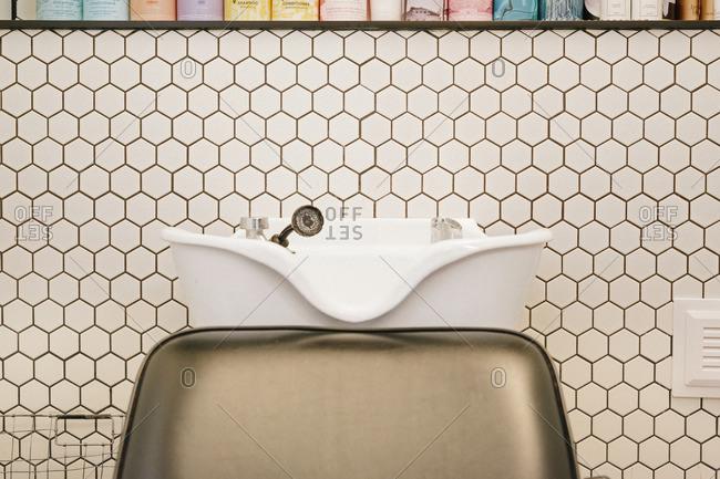 A hair salon hair washing basin and chair