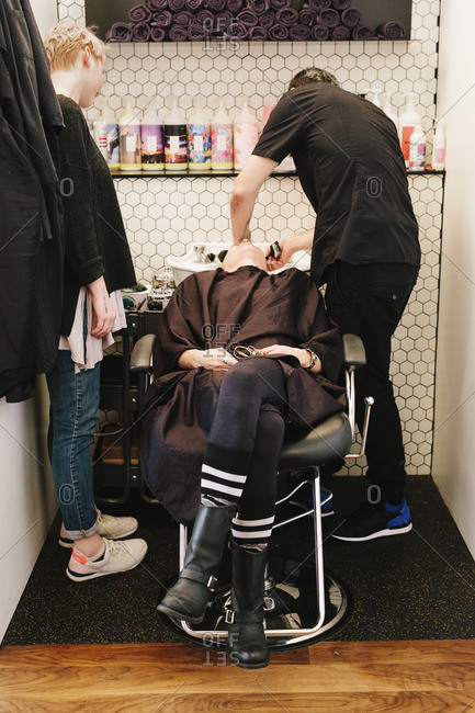 A client at a hair salon having her hair washed