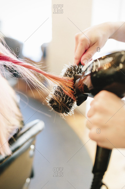 A hair stylist blow drying a client's long straight pink hair using a round bristle brush
