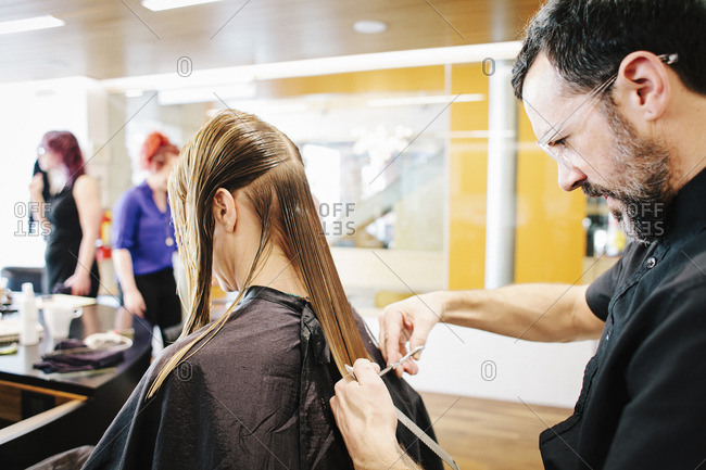 A hair stylist with a client, cutting her long straight hair