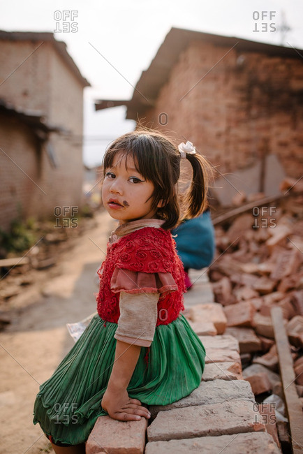 Nepal - March 19, 2016: Girl sitting outside on a crumbling brick wall