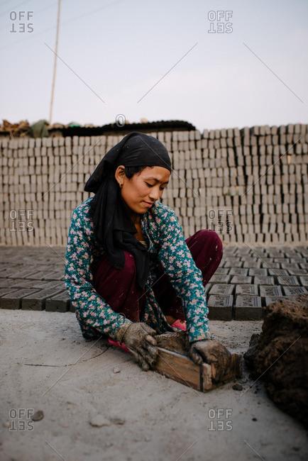 Nepal - March 19, 2016: Woman making bricks outside