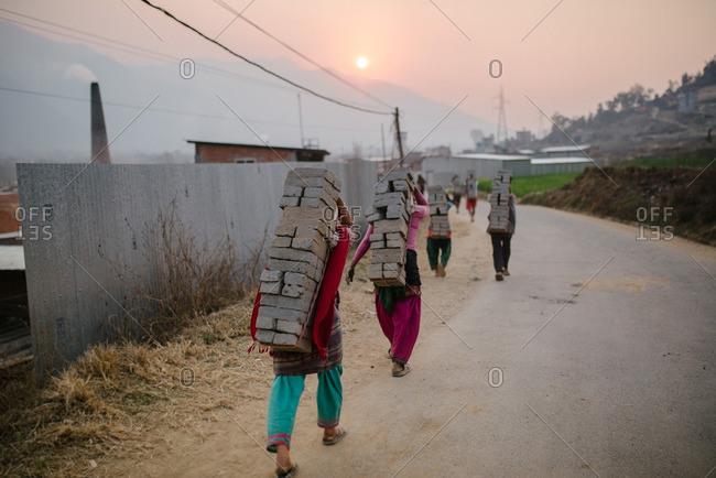 Nepalese men walking single file carrying loads of brick on their backs