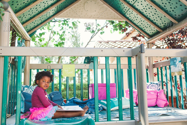 Girl reading in an outdoor play structure