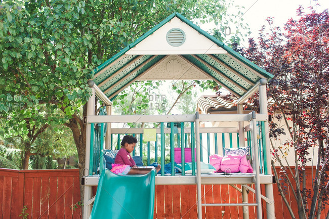 Girl sitting down in an outdoor play structure