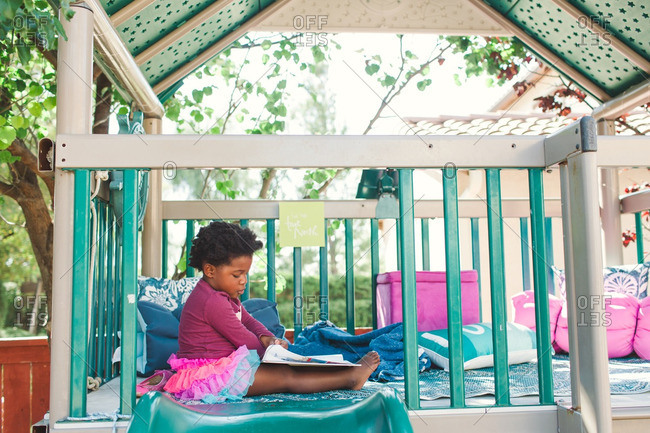 Girl reading a book in an outdoor play structure