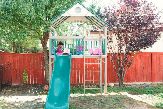 Girl sitting alone in an outdoor play structure