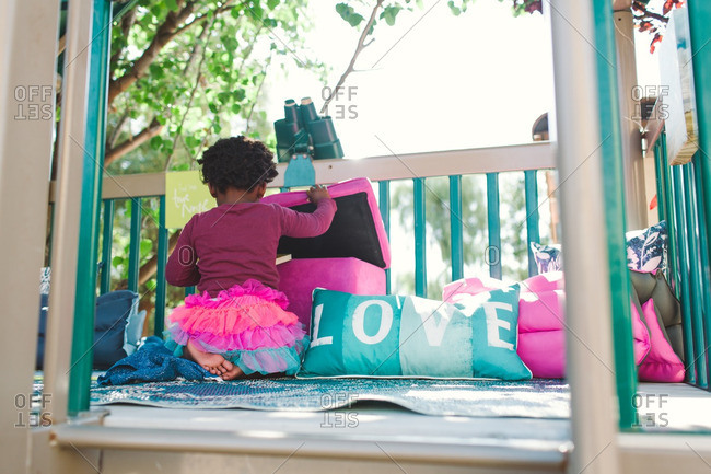 Girl looking for toys in an outdoor play structure
