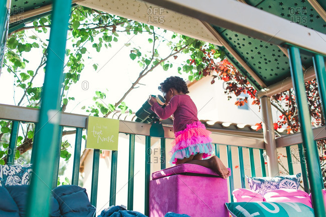 Girl looking through toy binoculars in an outdoor play structure