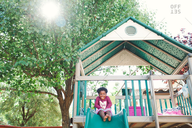 Girl sitting at the top of a slide on an outdoor play structure