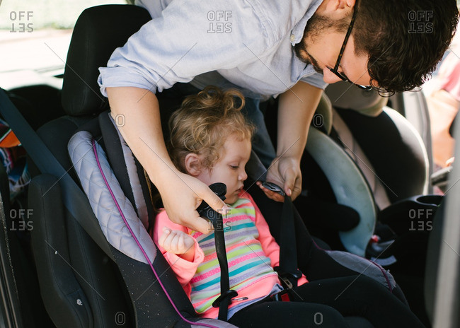 Father helping toddler get buckled into her carseat