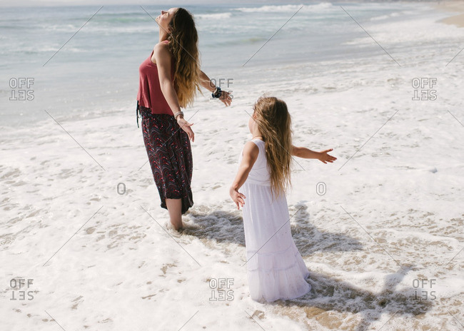 Mother and daughter standing in waves with arms spread