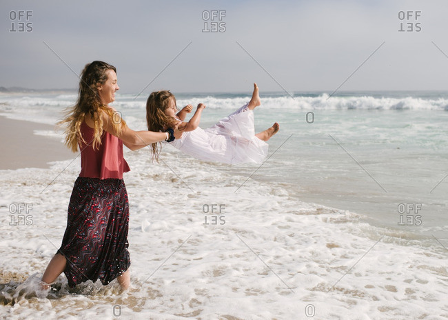 Mother pretending to throw daughter into the water