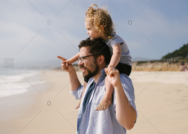 Father carrying toddler on his shoulders on a beach