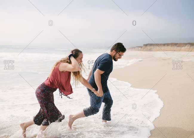 Husband and wife running through waves
