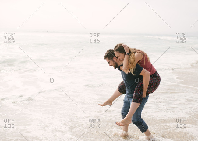 Husband carrying wife through waves