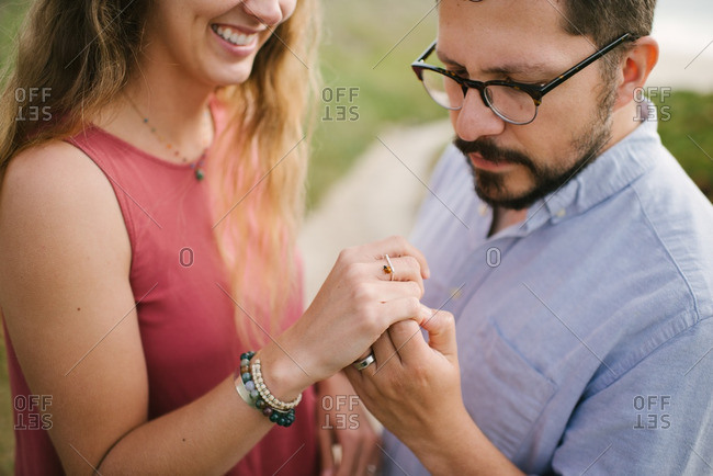 Husband looking at ladybug on his wife's hand