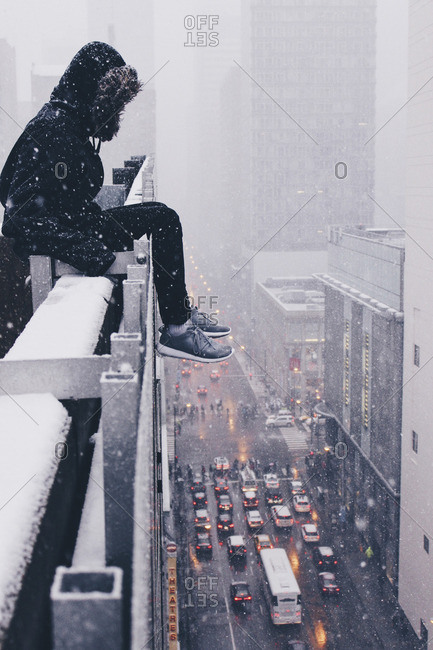 Person sitting on the ledge of a skyscraper in Chicago, Illinois in winter, snow and traffic
