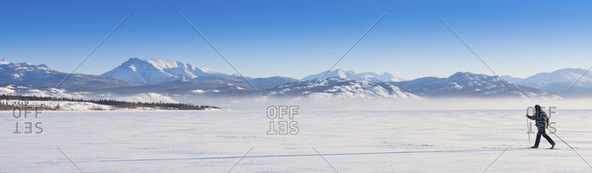 Cross country skier casting long shadow on untouched powder snow in a wide open wilderness landscape