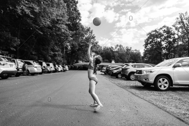 Young girl in parking lot throwing ball into air