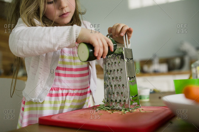 Girl grating zucchini on box grater
