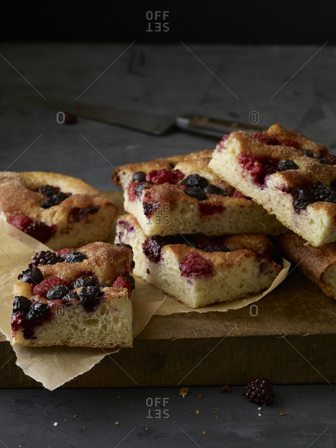 Cake squares with whole berries on a wooden cutting board