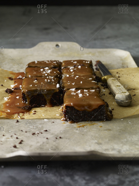 Sliced brownie squares with caramel sauce and sea salt on parchment paper