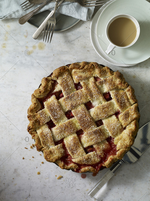 Fruit-filled pie with lattice crust and a cup of coffee
