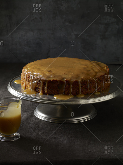 Cake on a stand covered in dripping caramel sauce