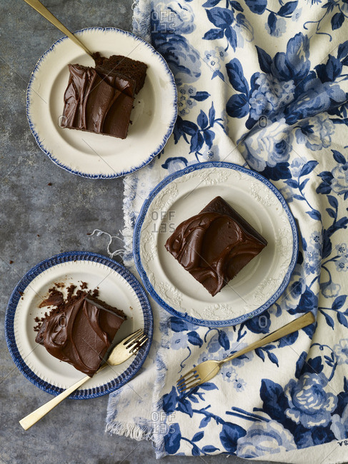 Chocolate-iced cake squares on blue and white china plates