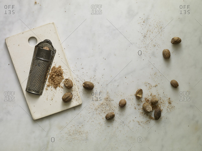 Whole nutmeg seeds and grater on a marble surface