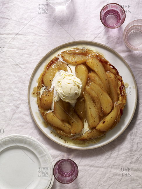 Sliced apple tart with a scoop of ice cream and pink glasses