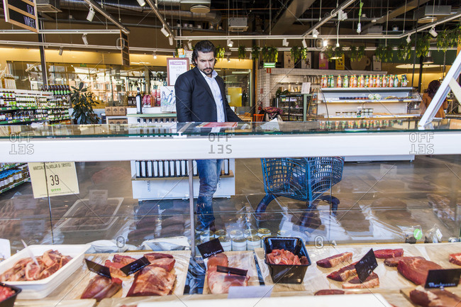 Man looking at meats in butcher's case