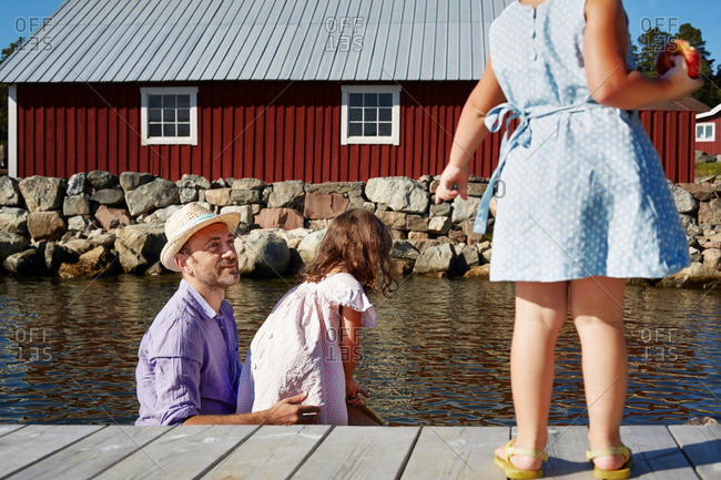 Father and two girls on pier, Utvalnas, Gavle, Sweden