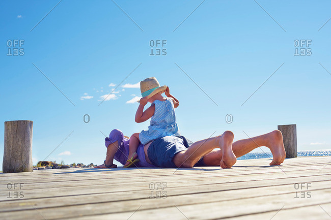 Female toddler and father on jetty, Utvalnas, Gavle, Sweden