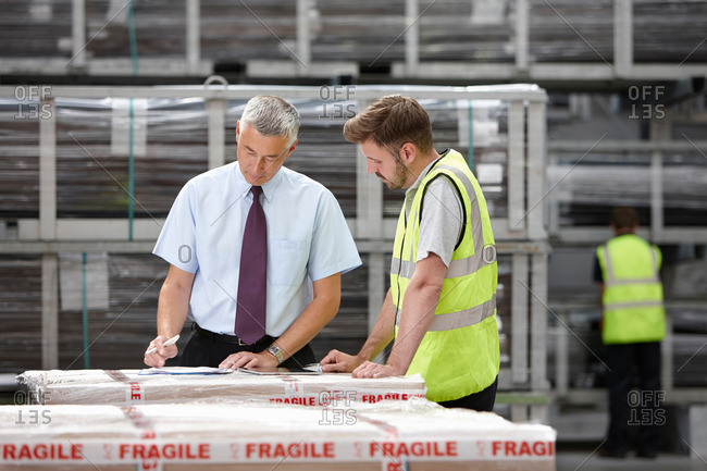 Warehouse worker and manager checking order in engineering warehouse