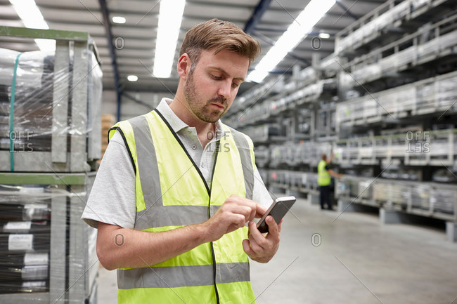 Portrait of worker using mobile phone in engineering warehouse