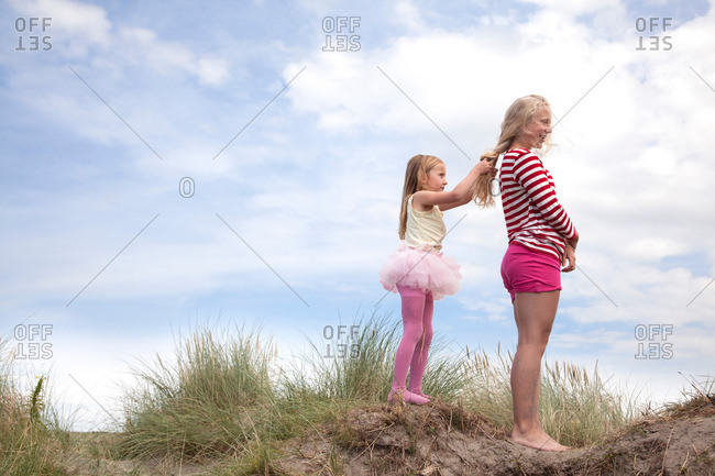 Two girls on dunes, one plaiting friend's hair, Wales, UK