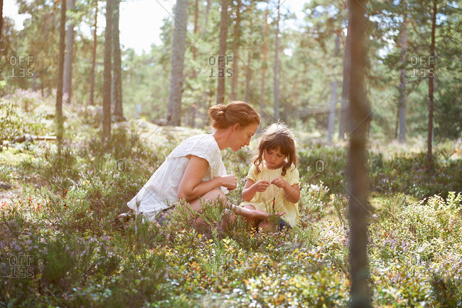 Mother and daughter sitting in long grass looking at plants