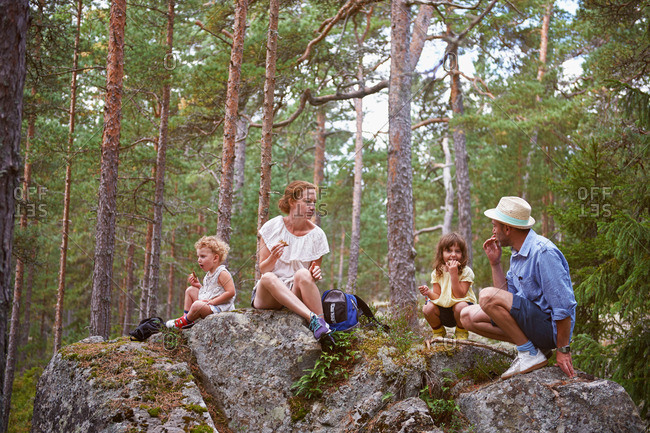 Family sitting on rocks in forest eating picnic