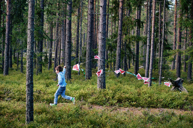 Boy running through forest pulling bunting