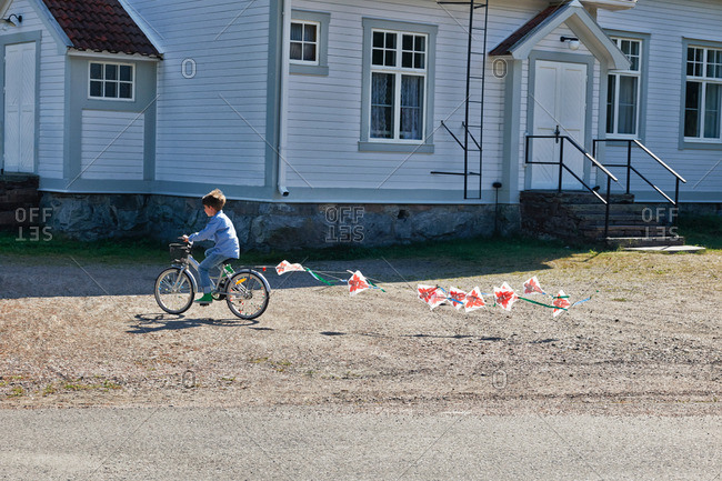Boy riding bicycle pulling bunting