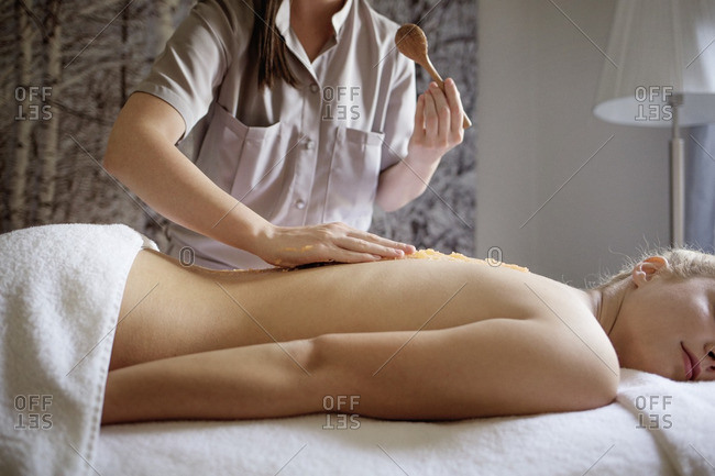 Midsection of massage therapist applying medicine on woman\'s back in spa