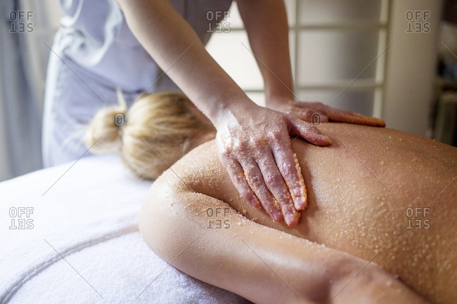 Midsection of therapist massaging woman\'s back in spa
