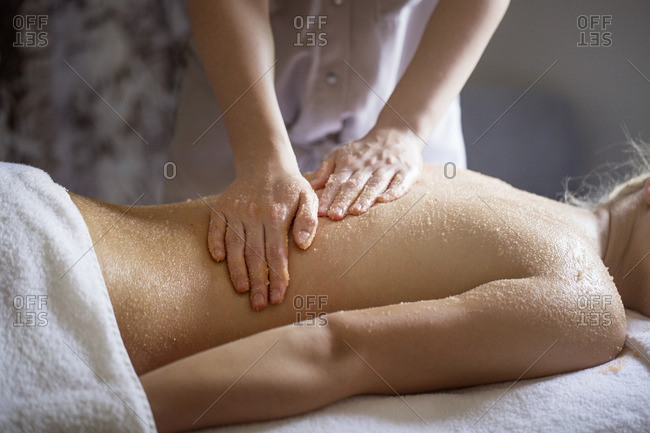 Midsection of female therapist massaging woman\'s back in spa