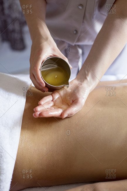 Midsection of therapist pouring essential oil on woman\'s back in spa