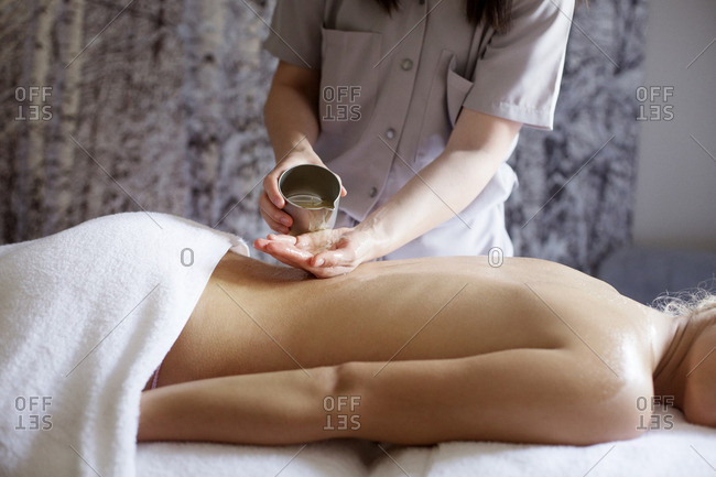 Midsection of female therapist pouring essential oil on woman\'s back in spa