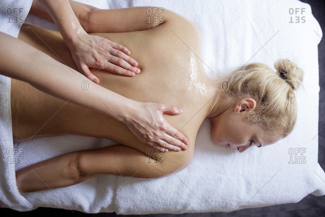 Overhead view of woman receiving back massage from therapist in spa