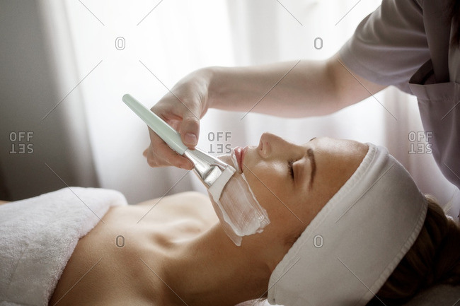Midsection of therapist applying facial mask on woman in spa