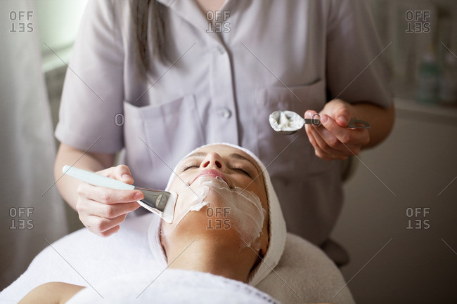Female therapist applying facial mask on woman in spa